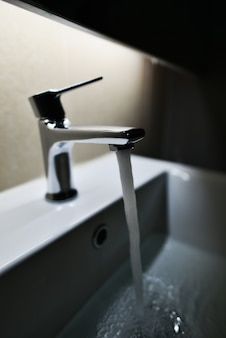 Chrome plated faucet with running water in the bathroom