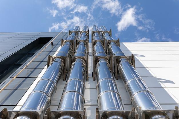 Хромированные вентиляционные трубы на внешней стене черно-белого промышленного здания на фоне голубого неба