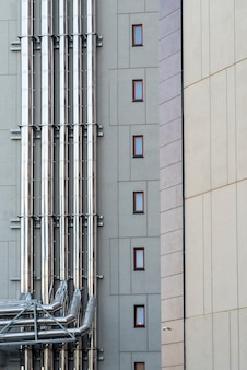 Chrome ventilation pipes on the wall of a modern facade building