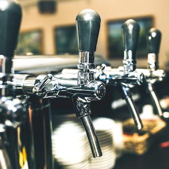 Хромированные краны для разливного пива в современном баре. деталь пивной машины, дозатор пива, крупный план, выборочный фокус, ретро-стиль, черный и белый