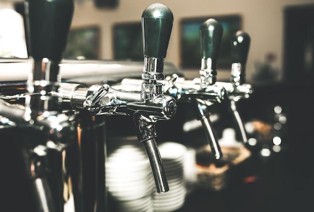 Хромированные краны для разливного пива в современном баре. деталь пивной машины, диспенсер для пива, крупный план, выборочный фокус, ретро-стиль, черный и белый