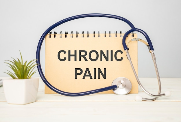 Chronic pain text on notebook and stethoscope