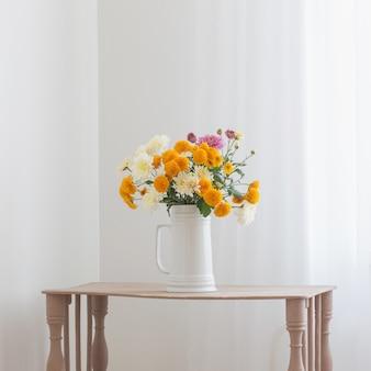 Цветы хризантемы в белом кувшине в белом интерьере