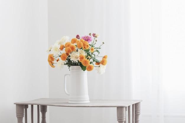 白いインテリアの白い水差しの菊の花