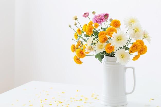 背景の白い壁に白い水差しの菊の花