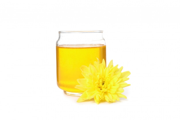Chrysanthemum and glass jar with honey isolated on white