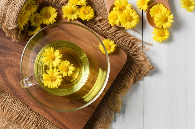 Chrysanthemum tea and chrysanthemum flower on white wood