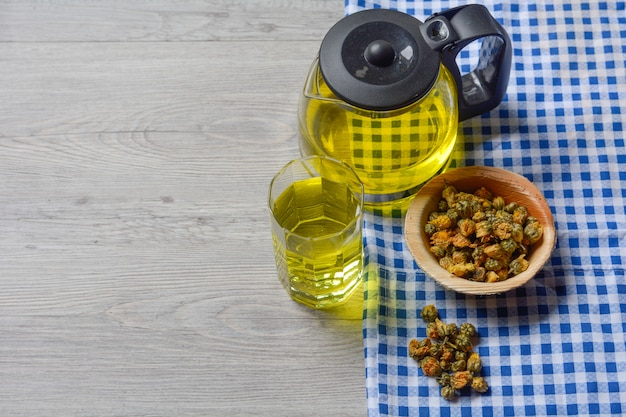 Chrysanthemum tea with dried chrysanthemum tea in a wooden bowl on the table