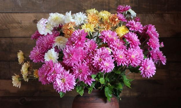 背景の庭の花束のクローズアップとして菊の秋の花