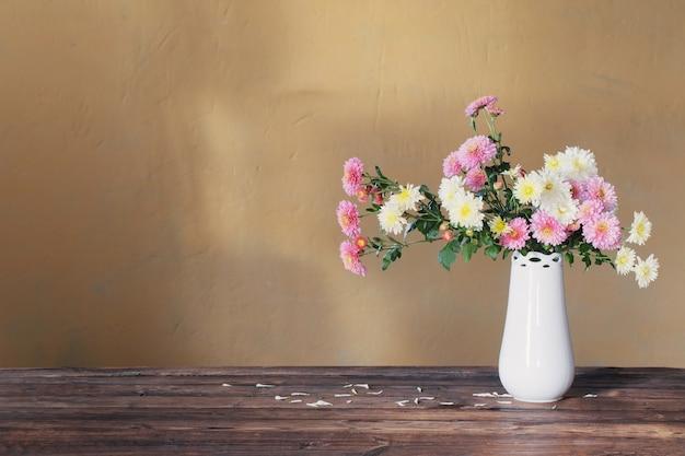 Хризантемы в вазе на старом деревянном столе