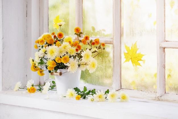 秋の窓辺の花瓶の菊