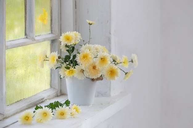 Chrysanthemums in vase on windowsill in autumn