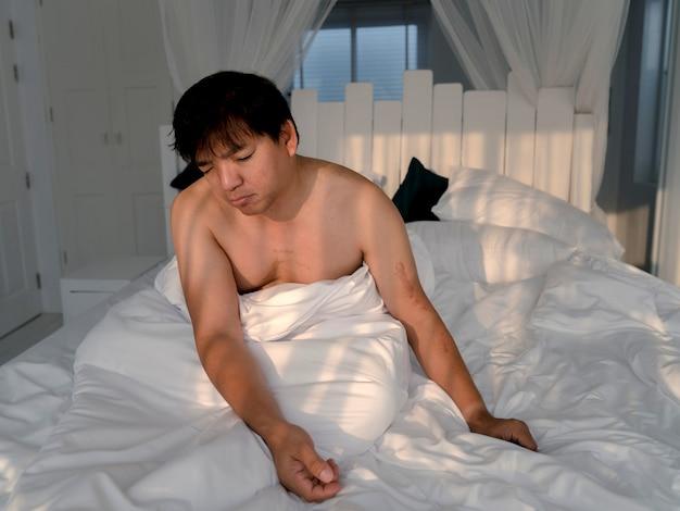 朝の白いベッドで起きた後に座って寝ているぽっちゃりアジア人男性