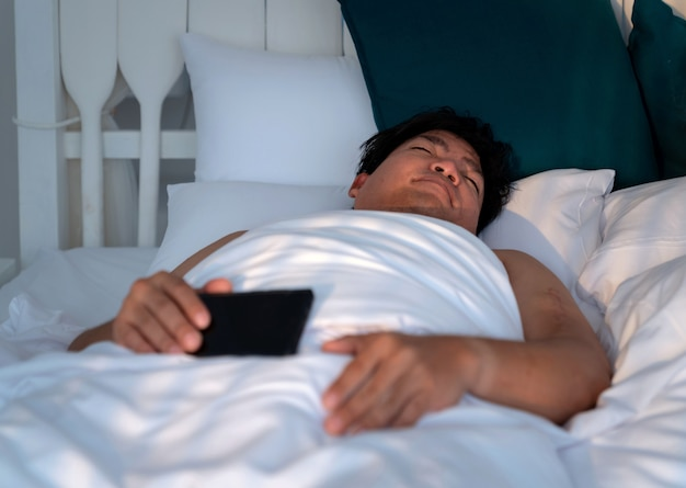 Пухлый азиатский мужчина спит в белой кровати, держа смартфон до утра