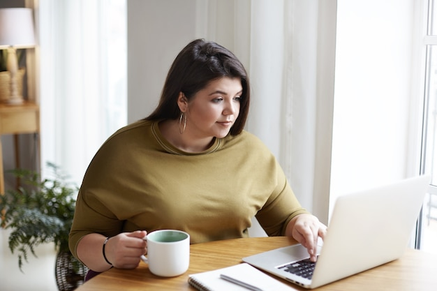 Chubby attractive young female freelancer wearing elegant sweater and round earrings working in front of open laptop, sitting in cozy home office interior, drinking coffee, browsing websites