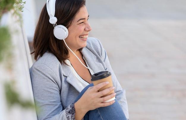 Ragazza paffuta che ascolta la musica all'aperto