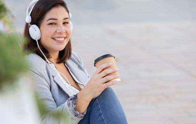 Пухлая девушка слушает музыку на открытом воздухе