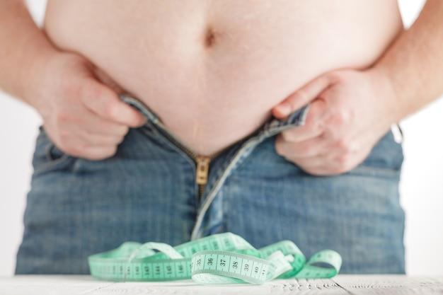 Пухлый мужчина не может застегнуть свои джинсовые брюки. концепция здоровья и похудения