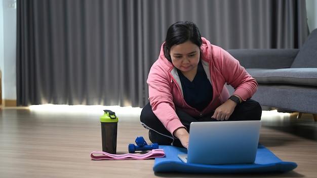 Пухлая пухлая молодая женщина смотрит видео тренировки фитнеса на компьтер-книжке дома.