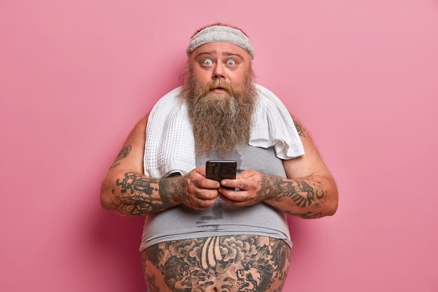 Chubby shocked man with thick beard busy with sport training, dressed in sportswear cares about his weight uses cellular for checking how much calories were burnt. sport, motivation