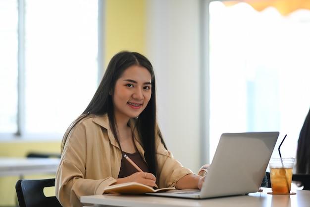 オンラインで学び、リモートオンライン教育を受けながらメモを取るぽっちゃり学生の女の子。