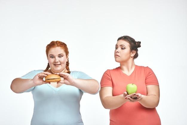 Пухлые женщины: одна женщина держит бутерброд, другая - яблоко.