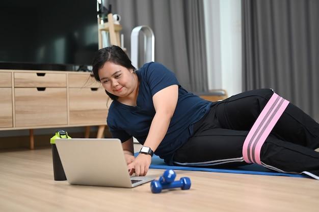 Пухлая молодая женщина упражнения и просмотр видео тренировки фитнеса на ноутбуке дома.