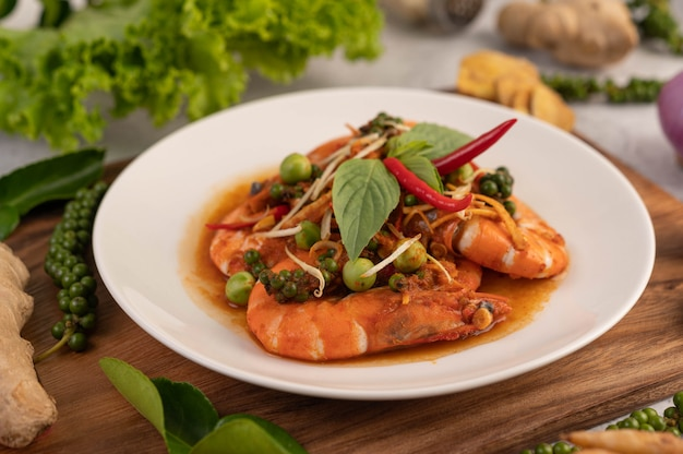Chuchi shrimp on a plate with fresh pepper seeds