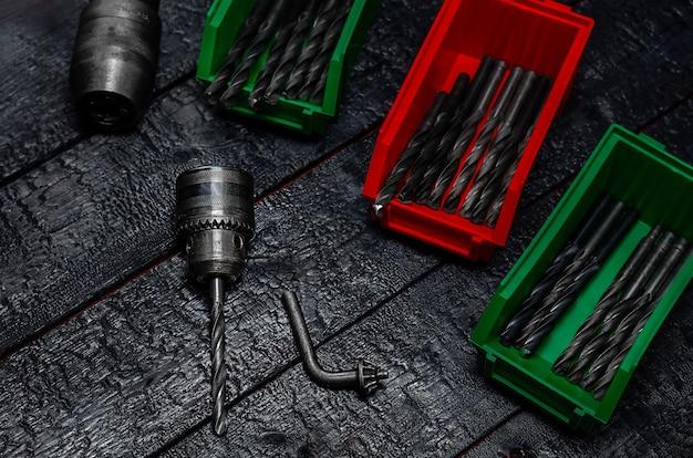 Патрон и сверла в красных и зеленых коробках на черной деревянной поверхности