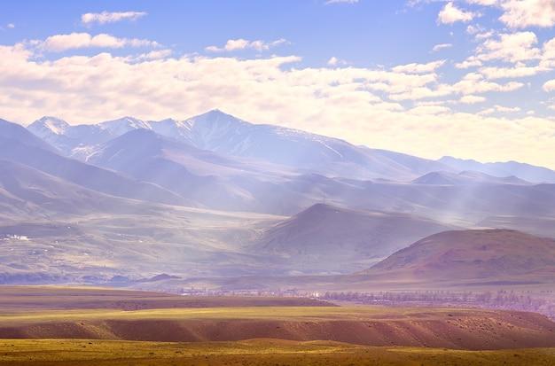 알타이 산맥의 추이 계곡 언덕의 구름 사이로 비스듬한 광선이 떨어집니다.