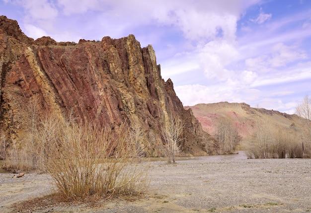 높은 바위를 배경으로 한 추야 강둑 알타이 산맥의 추이 계곡