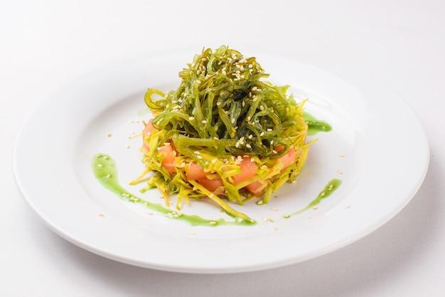 Салат чука в тарелке на белом