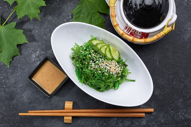 Chuka salad with cucumbers, sesame seeds and sauce, in a white plate, with a japanese teapot, chopsticks and maple leaves, on black concrete