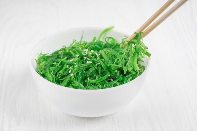 Салат из морских водорослей чука вакаме, украшенный кунжутом, подается в миске для еды бамбуковыми палочками