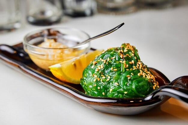 Салат из морских водорослей чукка с арахисовым соусом, лимоном и кунжутом