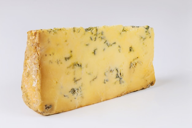 Chunk of roquefort cheese on white surface