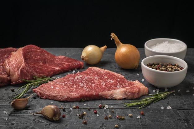 黒い木製のテーブルに牛肉とスパイスの塊。新鮮な肉のかけら。