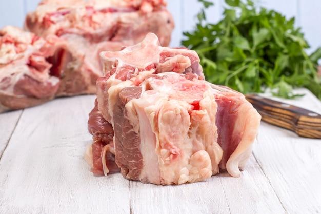 나무 배경에 신선한 생 쇠고기 꼬리 덩어리.