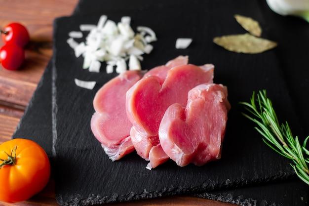 검은 슬레이트 배경에 얇게 썬 생 칠면조 고기, 다진 양파 덩어리.