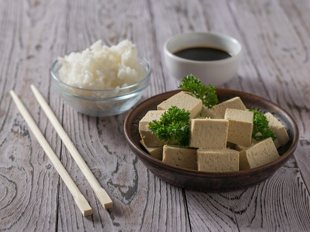 Chunks of tofu, rice, soy sauce and chopsticks on a wooden table. soy cheese. vegetarian product.