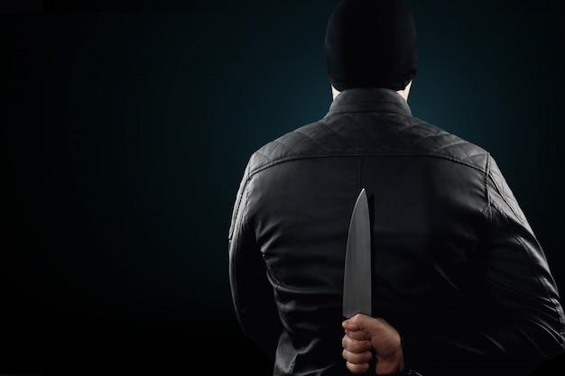 シリアルキラー、彼の頭の上にナイフと黒いchuolkomを持つマニアック