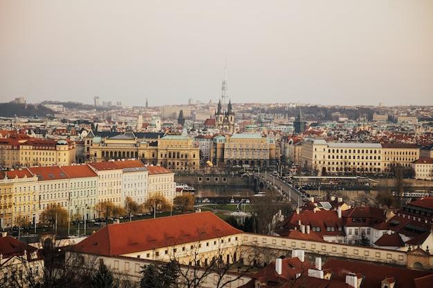 教会とプラハ城。プラハの歴史的な旧市街の赤い屋根と尖塔。