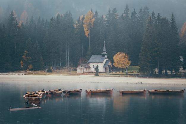 Церковь и деревянные лодки на лаго ди браи унылое изображение, сделанное во время дождя в осенний сезон, доломиты, италия