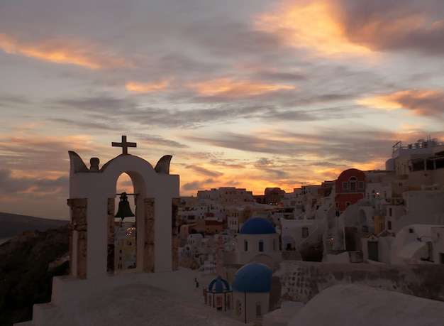Church bell tower against pastel color of evening sky, oia village, santorini island, greece