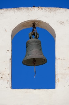 Church bell on a white bell tower against a blue clear sky