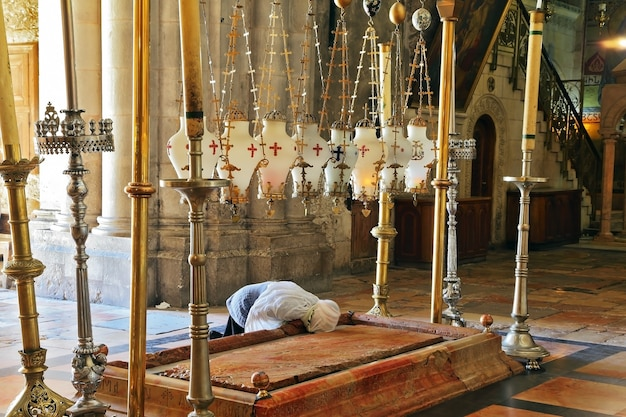 Church of the holy sepulcher in jerusalem. pilgrim prays in a white veil over the stone of unction