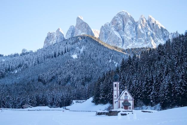 Церковь в заснеженном лесу под доломитовыми альпами