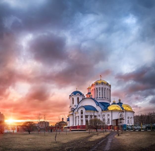 ピンクの夕焼け空の下でモスクワのビビレボにあるすべてのモスクワ聖人教会