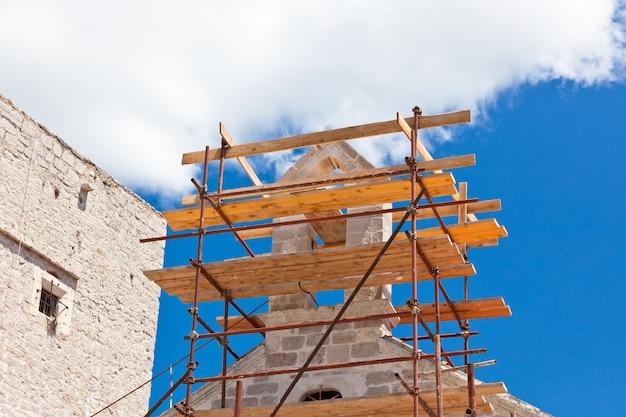 푸른 하늘 배경에 교회 복원 비계