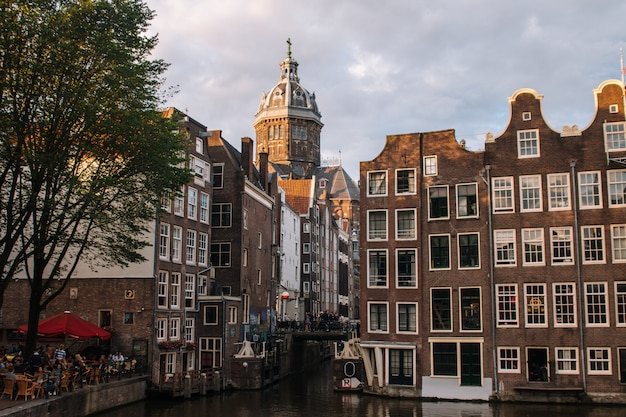 Church of saint nicholas dominating the main canal from red lights district at the center of amsterdam, holland, the netherlands.